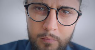 Progressive caucasian freelancer in eyeglasses with ponytail turn to camera being thoughtfull and serious. Progressive caucasian freelancer in eyeglasses with stock video
