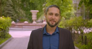 Progressive hipster businessman walks to camera and smiles into it being happy and positive in park. Progressive hipster businessman walks to camera and smiles stock footage