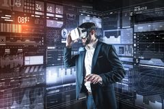 Progressive specialist wearing virtual reality glasses while working. New vision. Clever enthusiastic young programmer feeling interested while being in his Stock Photos