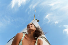 Progressive young girl on a blue sky background. Cool teen next to a windmill. Youth is a future concept. Copy space. royalty free stock image