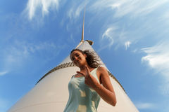 Progressive young girl on a blue sky background. Cool teen next to a windmill. Youth is a future concept. Copy space. stock images