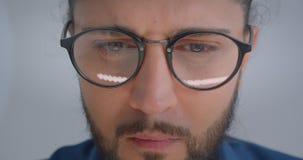 Progressiver kaukasischer Freiberufler in den Brillen mit dem Pferdeschwanz, der konzentriert und beschäftigt ist stock video