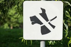 Prohiba a perros la muestra de la bandera establecida en zona verde del parque con el fondo verde imagen de archivo libre de regalías