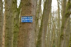 Prohibited to pass for unauthorized persons in Dutch on a tree. The blue and white coloured Dutch sign Prohibited to pass for unauthorized persons stuck high on stock images