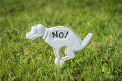 Prohibited to poop. Metal sign of dog placed on the green lawn prohibiting dogs to poop on the grass royalty free stock photos