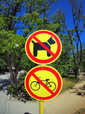 Prohibiting signs no-dogs and no-bikes in the park. Photographed sunny summer day with wide angle fisheye lens and distortion view Royalty Free Stock Photo