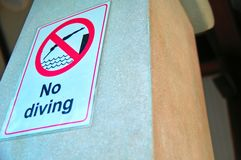Prohibition plate `No diving` on the concrete column. Warning sign. Concept safety in pool. stock photography