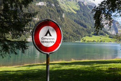 Prohibition sign Campieren Verboten. Alps. Switzerland. Round iron prohibition sign near the lake on background of mountains. Alps. Switzerland Royalty Free Stock Image
