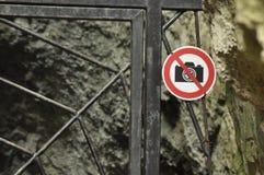 A proibição em fotografar o objeto Um sinal no metal da porta da entrada As cavernas no parque nacional foto de stock