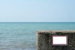 Proibindo o sinal isolado vazio instalado no Pebble Beach do cais Imagem de Stock Royalty Free