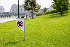 Proibindo o sinal você não pode andar com um cão no gramado verde Não andando nenhum animal fotografia de stock royalty free