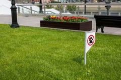 Proibindo o sinal você não pode andar com um cão no gramado verde Não andando nenhum animal fotografia de stock