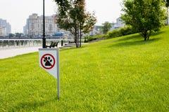 Proibindo o sinal você não pode andar com um cão no gramado verde Não andando nenhum animal fotos de stock
