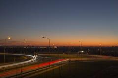 Projétis luminosos da rua da opinião da noite com por do sol mágico na cidade de Letónia Daugavpils Fotografia de Stock