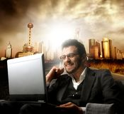 Project. Young businessman smiling and using a laptop on a cityscape background royalty free stock photos