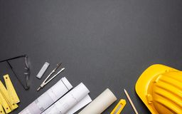 Project blueprints, yellow hardhat and engineering tools on black royalty free stock image