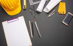 Project blueprints, yellow hardhat and engineering tools on black stock photo