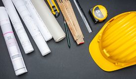 Project blueprints, yellow hardhat and engineering tools on black stock photos