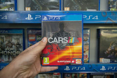 Project Cars. Bratislava, Slovakia, circa april 2017: Man holding Project Cars videogame on Sony Playstation 4 console in store Royalty Free Stock Photos