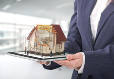 Project concept. Demonstration of an architectural project. Man draws a house project on the tablet royalty free stock photo