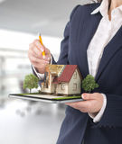 Project concept. Demonstration of an architectural project. Man draws a house project on the tablet stock image