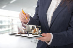 Project concept. Demonstration of an architectural project. Man draws a house project on the tablet stock photography