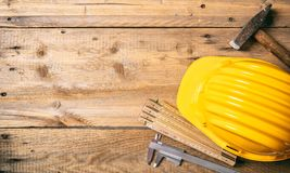 Project construction. Yellow hard hat and tools on wooden desk, copy space, top view stock photography