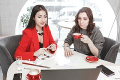 Project creation process. Two girls designers are working with laptop and documentation at the project sitting at the royalty free stock photo