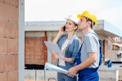 Project developer and construction worker on site using technology royalty free stock image