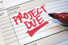 Project due. Written in red on calendar in book Stock Image