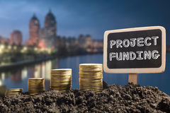Project funding. Financial opportunity, business and intertnet concept. Golden coins in soil Chalkboard on blurred urban. Background Stock Photo