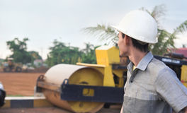 Project leader. Man at field froject with heavy machines at background Stock Photo