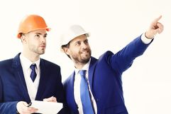 Project management, building, construction concept. Businessman and young worker with smiling and serious faces. Happy. Boss pointing something to employee Stock Image