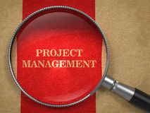 Project Management Through Magnifying Glass. Project Management Concept. Text on Old Paper with Red Vertical Line Background through Magnifying Glass Stock Photos
