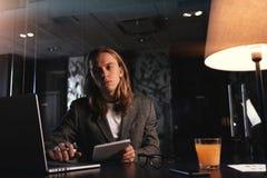 Project manager alla moda stanco che lavora dal computer portatile contemporaneo all'ufficio di notte I pantaloni a vita bassa co Fotografie Stock Libere da Diritti