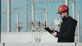 Project manager checking object. And writing down notes. Electrical station at background stock footage