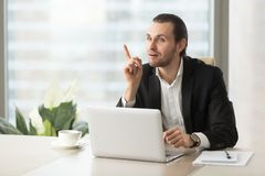 Young businessman suddenly got great idea at work desk. Project manager sitting in front of laptop with forefinger raised up. Young entrepreneur suddenly got Stock Image
