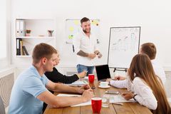 Project presentation. Young hipsters businessmen and women. Month plan presentation. Young happy businessmen and women group at modern office, team discussion at Royalty Free Stock Images