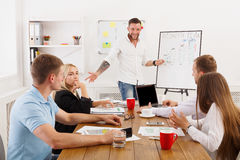 Project presentation. Young hipsters businessmen and women. Month plan presentation. Young happy businessmen and women group at modern office, team discussion at Royalty Free Stock Photography