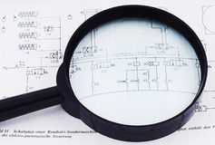 Project under the magnifying glass. Hydraulic schematics with magnifying glass on it suggesting deep project analysis Stock Photography