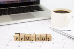 Project wording, calendar and laptop on office table Stock Images