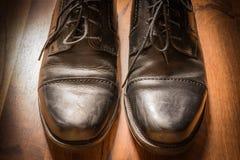 Projecteur en bois S de lumière du soleil de plancher porté par chaussures élégantes en cuir noires Images stock
