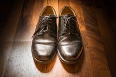 Projecteur en bois S de lumière du soleil de plancher porté par chaussures élégantes en cuir noires Photo libre de droits
