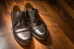 Projecteur en bois S de lumière du soleil de plancher porté par chaussures élégantes en cuir noires Photos libres de droits