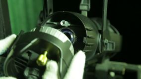 Projecteur théâtral de profil avec lequel le bloc d'éclairage dans les gants fonctionne des changements la lampe d'halogène banque de vidéos
