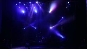 Projecteurs bleus de clignotant qui illuminent l'étape à un concert avec le brouillard banque de vidéos