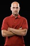 Projectile de l'homme chauve sérieux posant avec des bras croisés Photos libres de droits