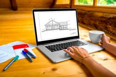 Projecting a house. Architects projecting stuff, laptop with drawing, markers and coffe cup on the wooden floor in the cottage Royalty Free Stock Image