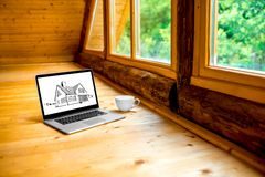 Projecting a house. Laptop with drawing and coffe cup on the wooden floor near the window in the cottage Royalty Free Stock Image