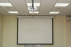 Projection screen in the boardroom with overhead projector Royalty Free Stock Photography